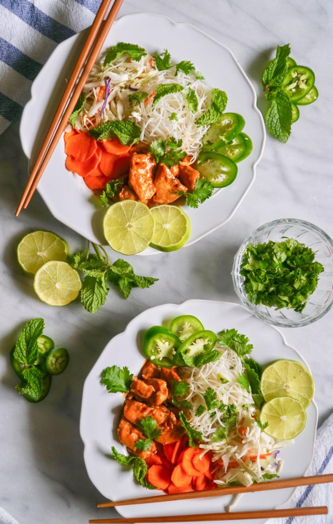 Vietnamese Noodle bowl with spicy peanut chicken, limes, jalapeños,  carrots with fresh herbs sprinkled around the bowls and chopsticks.