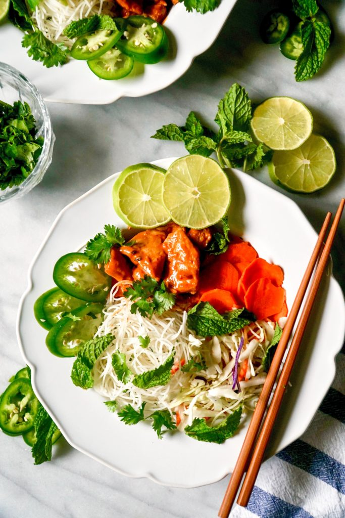 Vietnamese Noodle bowls with spicy peanut chicken, limes, jalapeños, and carrots
