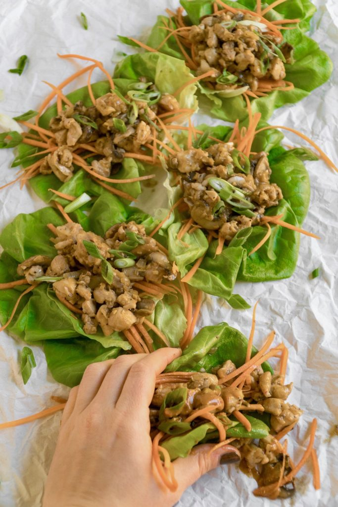 Hand reaching for some delicious peanut chicken lettuce wraps